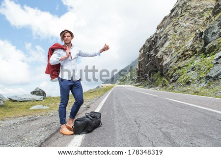 portrait of a young fashion man hitchhiking in the mountains with a smile on his face - stock photo