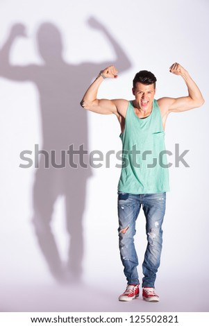portrait of a young fashion man showing his biceps muscles with a shouted pride, on gray with hard shadow - stock photo
