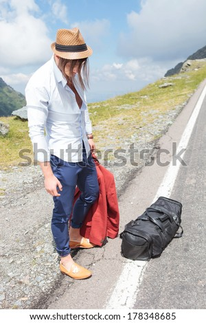portrait of a young fashion man standing on the road side with a bag at his feet, looking down while holding his jacket in his hand - stock photo
