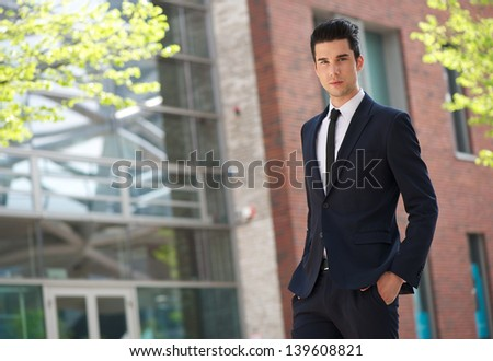 Portrait of a young fashionable businessman walking to work - stock photo