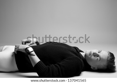Portrait of a young fashionable man in trendy clothes lying over gray background. Perfect haircut. Hipster style. Copy-space. Black and white (monochrome) studio shot - stock photo