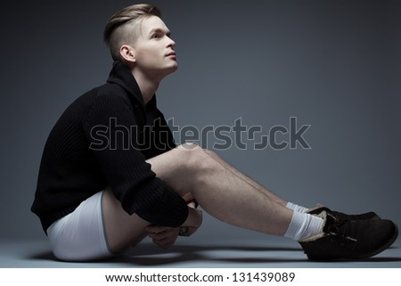 Portrait of a young fashionable man in trendy clothes sitting over gray background and holding his legs with hands crossed. Perfect haircut. Hipster style. Studio shot - stock photo