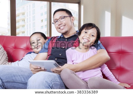 Portrait of a young father and his children smiling at the camera while holding a digital tablet on the sofa at apartment