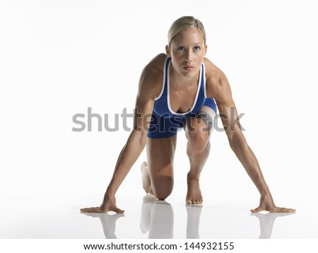 Portrait of a young female athlete in starting position against white background - stock photo