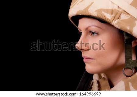 Portrait of a young female British soldier in profile, against a black background. - stock photo