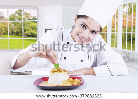 Portrait of a young female chef garnishing food in the kitchen - stock photo