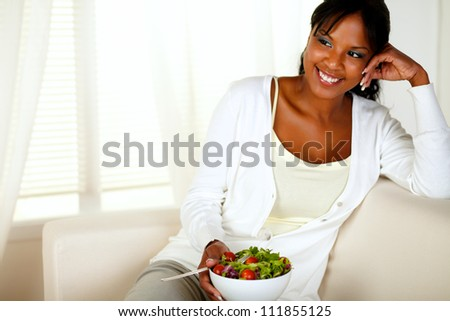 Portrait of a young female eating healthy salad lunch while sitting on couch at home indoor. With copyspace. - stock photo
