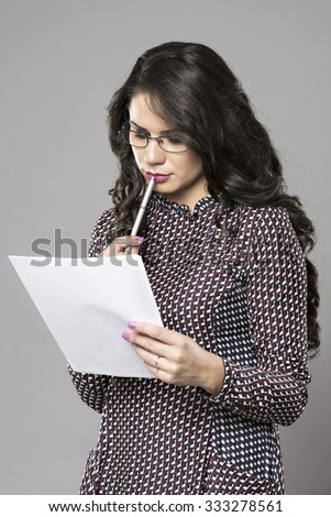 Portrait of a young female entrepreneur thinking while taking notes - stock photo