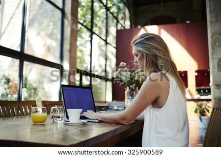 Portrait of a young female freelancer using laptop computer for distance job while sitting in modern coffee shop interior, smart blonde woman working on net-book during morning breakfast in cafe bar - stock photo