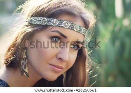 Portrait of a young female hippie with headband and earrings - stock photo