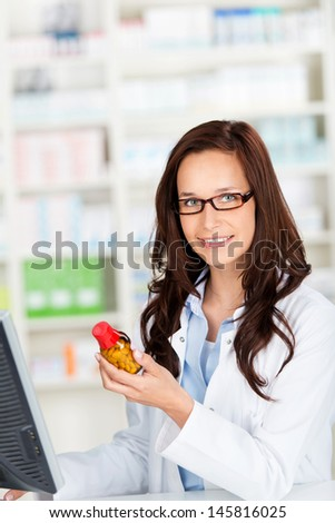 Portrait of a young female pharmacist checking the medication - stock photo