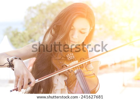 Portrait of a young female playing the violin. With sunshine. Color toned image. - stock photo