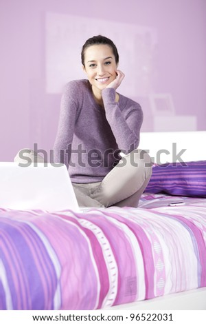 Portrait of a young female relaxing in bed while using laptop - stock photo