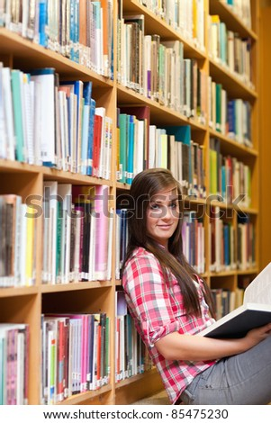 Portrait of a young female student holding a book in a library