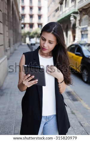 Portrait of a young female student reading news on touch pad while standing in urban setting, modern tourist woman dressed in stylish clothes using digital tablet computer while walking on the street - stock photo