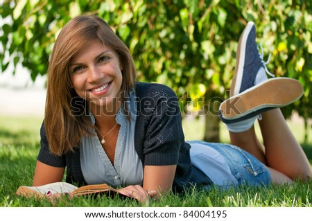 Portrait of a young female student with book at the campus - stock photo