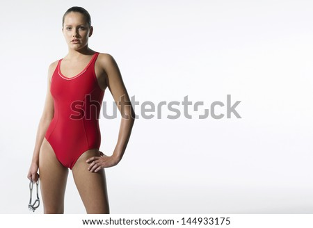 Portrait of a young female swimmer standing against white background - stock photo