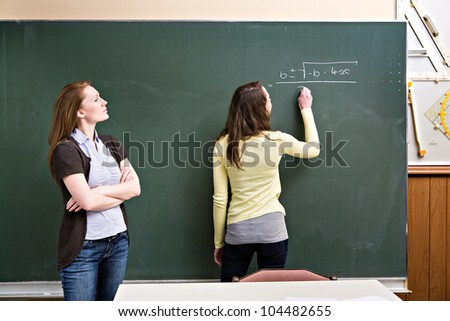 portrait of a young female teacher and a schoolgirl in the classroom