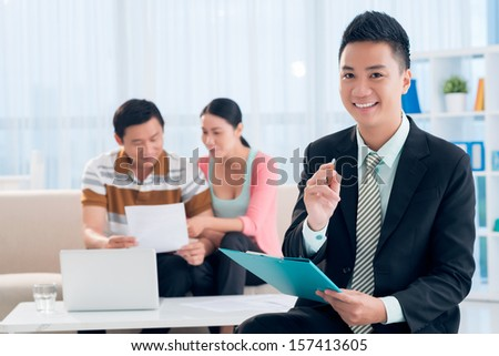 Portrait of a young financial broker with a clipboard in hands smiling and looking at camera on the foreground - stock photo