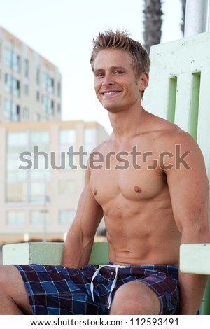 portrait of a young, fit, handsome lifeguard on the beach - stock photo