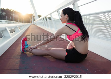 Portrait of a young fit woman dressed in sportswear stretching legs muscles before start her morning run outside in summer day, female jogger do physical exercises outdoors, sporty girl working out    - stock photo