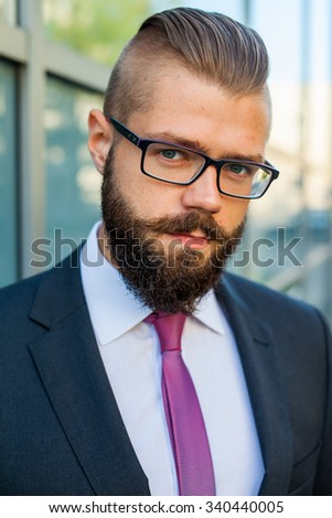 Portrait of a young focused bearded businessman outside the office building