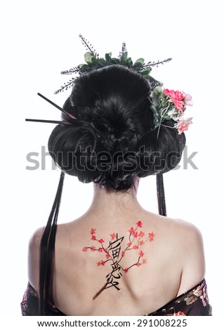 Portrait of a young geisha girl. Drawing cherry and hieroglyphs on the back. The concept of Asian beauty. - stock photo