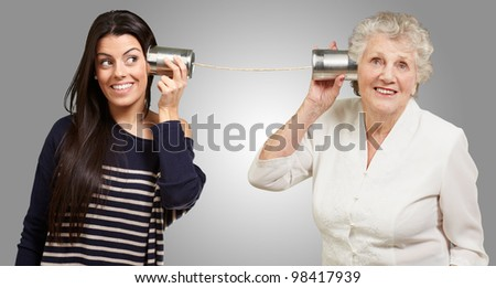 portrait of a young girl and her grandmother hearing sounds using a metal tin can over a grey background