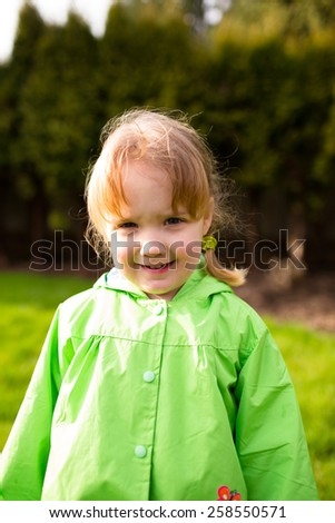 Portrait of a young girl at a park with a rain coat on. This lifetsyle photo was shot with natural light.