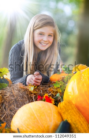 portrait of a young girl between pumpkin and straw - stock photo