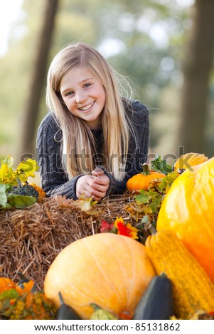 portrait of a young girl between pumpkin and straw