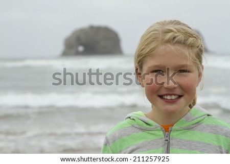 Portrait of a young girl by twin rocks on Rockaway beach Oregon - stock photo