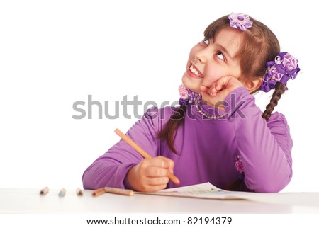 portrait of a young girl drawing at table - stock photo