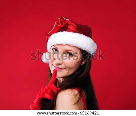 Portrait of a young girl dressed as Santa Claus on a red background. Happy New Year and Merry Christmas!