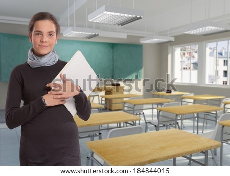 Portrait of a young girl holding a book in a classroom - stock photo