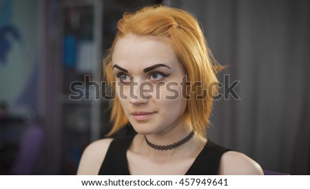Portrait of a young girl in a beauty salon. The client waits for her master in the chair, her bob and red hair. - stock photo
