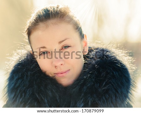 Portrait of a young girl in a fur collar sunlit