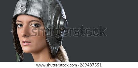 Portrait of a young girl in a leather helmet pilot on a gray background. Studio, close-up