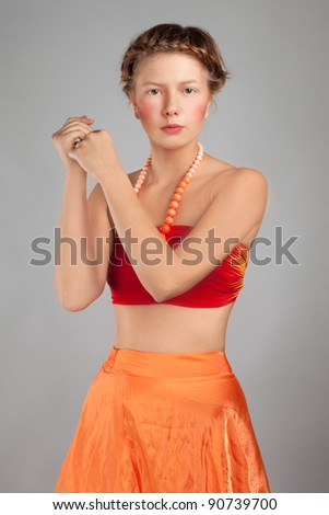 portrait of a young girl in an orange dress in the studio - stock photo