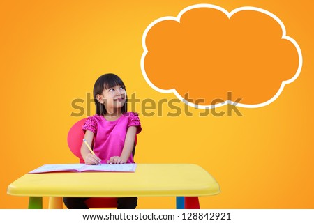 Portrait of a young girl in school at the desk. Daydreaming. Blank cloud with copyspace for your text and logo - stock photo