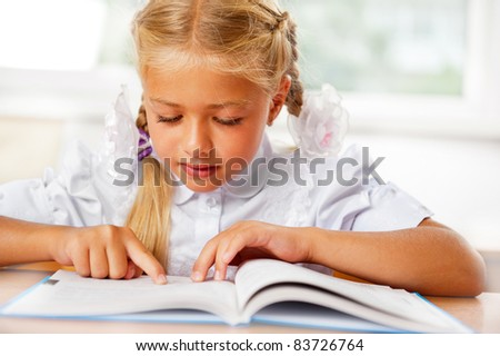 Portrait of a young girl in school at the desk. Horizontal Shot. She is very keen on reading