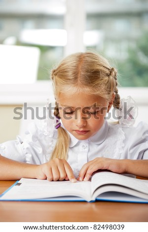 Portrait of a young girl in school at the desk. Vertical Shot. She is very keen on reading