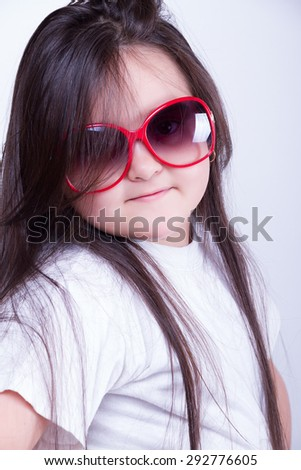Portrait of a young girl in sunglasses on a gray background