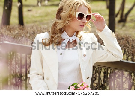 Portrait of a young girl in sunglasses waiting for somebody in park  - stock photo