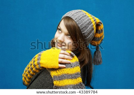 Portrait of a young girl in winter clothes looking up against blue textured wall - stock photo