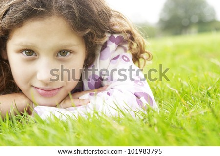 Portrait of a young girl laying down on green grass in the park, smiling at camera. - stock photo