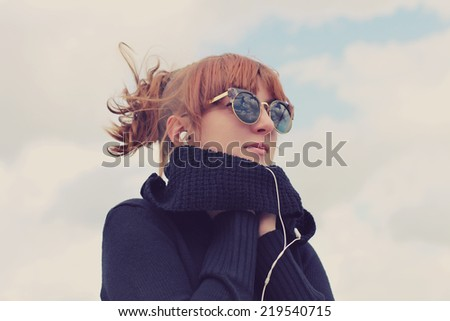 Portrait of a young girl listening to music in earphones from smart phone mp3 player outdoors. Photo toned style Instagram filters - stock photo