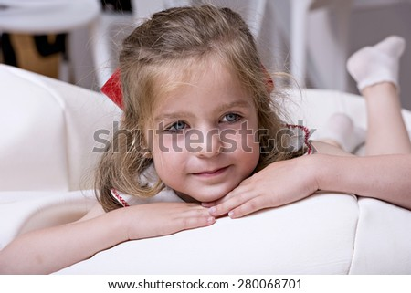 Portrait of a young girl lying, looking at the camera