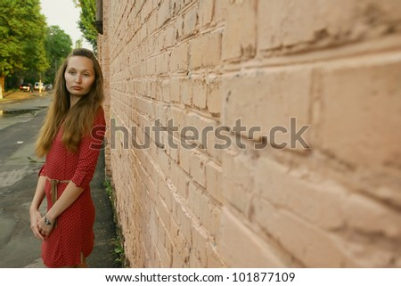 portrait of a young girl near a brick wall - stock photo