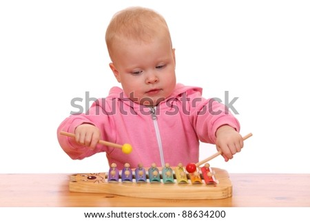 Portrait of a young girl playing a toy xylophone - stock photo